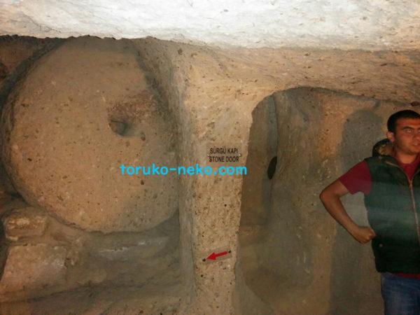 カイマクル地下都市の石でできた扉を説明する男性